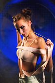 Sultry Beautiful Young Gymnast Woman With A Slim Sport Body Posing With Gymnastics Tape On A Dark Ba poster