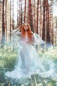 Beautiful Redhead Woman Forest Nymph In A Blue Transparent Light Dress In The Woods Spinning In Danc poster