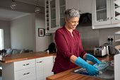 Senior woman washing dishes in her kitchen. Cheerful mature housewife in kitchen. Beautiful smiling  poster