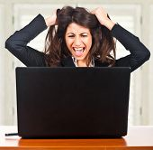 stock photo of irritated  - Businesswoman getting crazy in front of her laptop - JPG