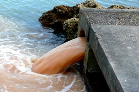 stock photo of water pollution  - Some polluted water sewage or waste product gushing from a pipe into the sea next to a beach - JPG