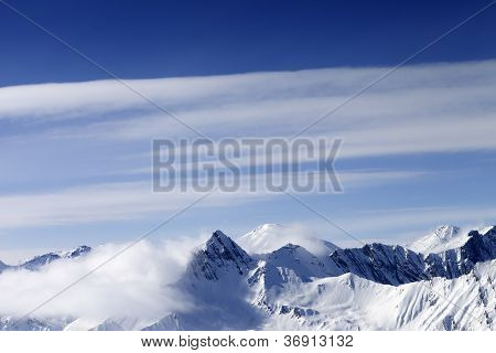 High Mountains In Haze And Blue Sky With Clouds