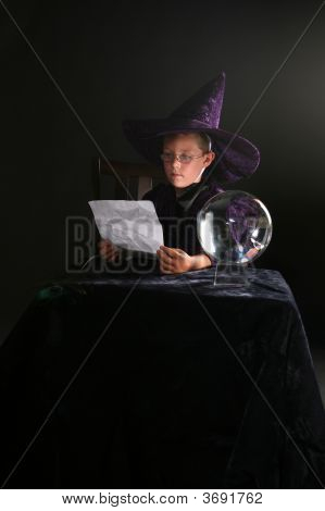 Child In Wizard Costume Consulting His Spell