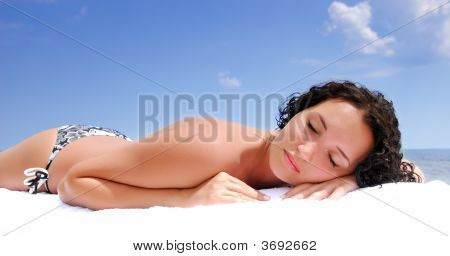 Female Lying Down On Beach Under Summer Sun