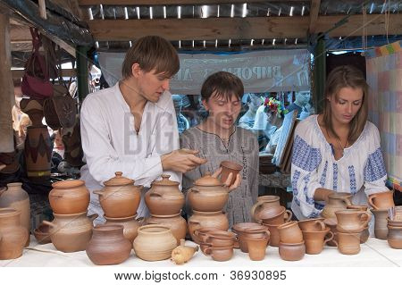 Two guys and a girl selling pottery.