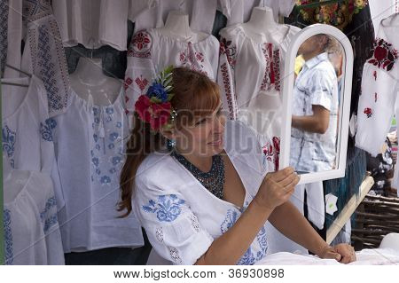 Cheerful woman sells embroidery, made with his own hands.
