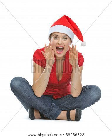 Young Woman In Christmas Hat Shouting Through Megaphone Shaped Hands