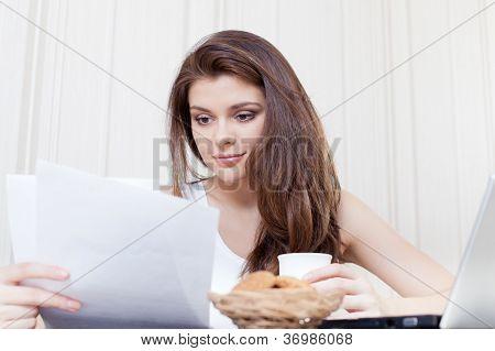 Happy woman enjoying tea and cookies