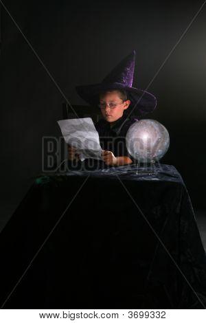 Assistente criança lendo uma mágica ao lado de uma bola de cristal