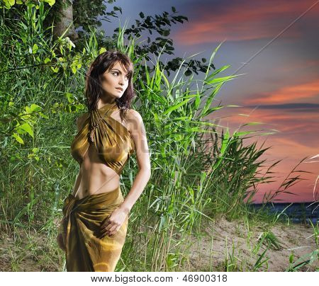 Attractive savage woman is posing in the jungle over the sunset background