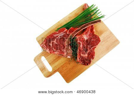 fresh spare ribs : raw pork with thyme and green chives on wooden board isolated over white background