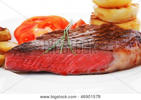 meat savory : grilled beef fillet served on white plate with tomatoes and potatoes isolated over white background