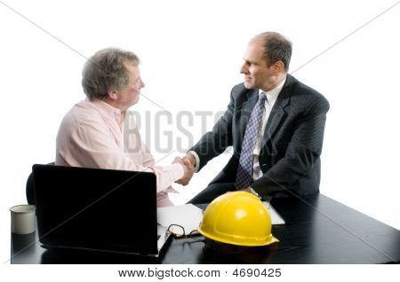 Two Business Partners At Desk Shaking Hands