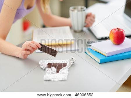 Closeup On Teenage Girl Eating Chocolate While Studying In Kitch