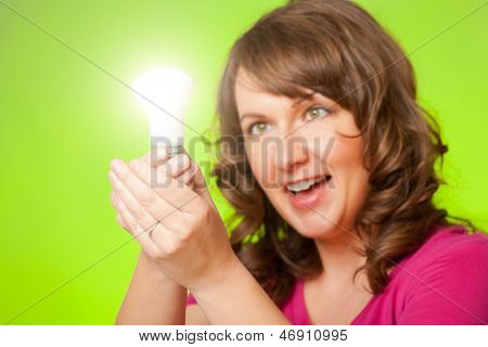 Woman with bulb in hand, could be a concept of new idea or ecology because of green background