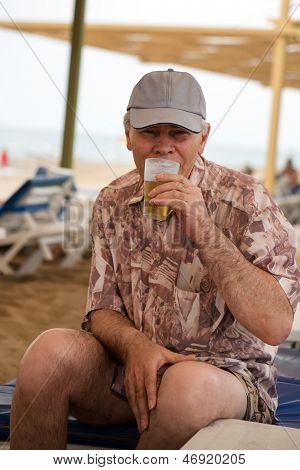 Senior Man Enjoying Drinking Beer On Beach