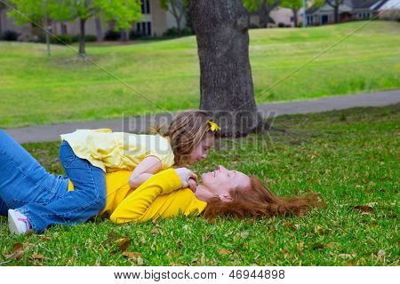 Filha e mãe jogar deitado no gramado do parque ao ar livre, vestida de amarelo