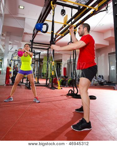 Crossfit fitness Kettlebells swing and flying exercise man and woman workout at gym