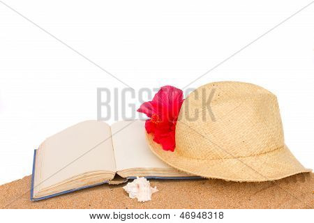 straw hat ans book on sand