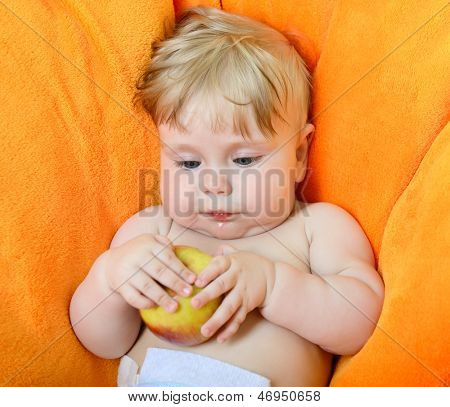portrait of little baby boy eating an apple