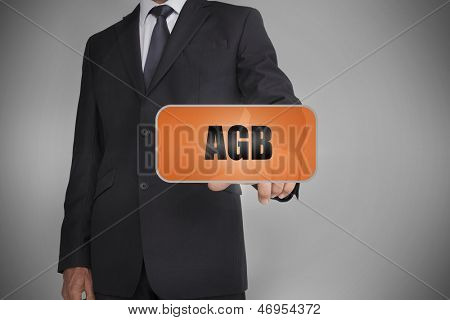 Businessman touching orange tag with the word agb written on it on grey background