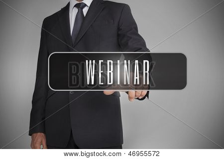 Businessman selecting label with webinar written on it on grey background