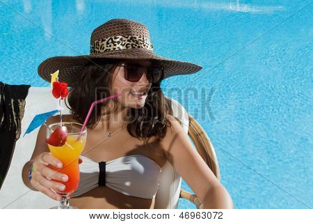 Young beautiful woman outdoors sitting on the couch near swimming-pool drinking a fresh cocktail