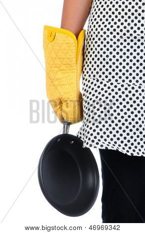 A woman holding a frying pan by her side. She is wearing a polka dot apron and a yellow oven mitt. Vertical format over a white background.