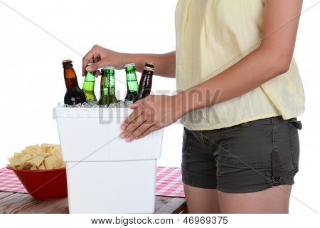 Closeup of a woman taking a beer bottle from a styrofoam ice chest on a picnic table with checkered table cloth and bowl of chips. Isolated on a white background. Woman is not recognizable.