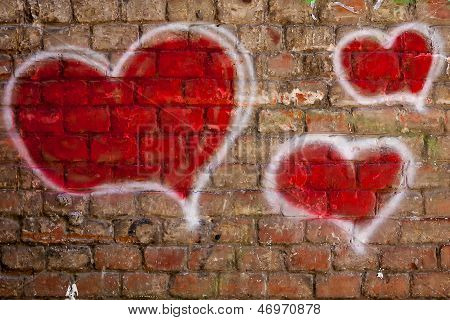 red hearts painted on a brick wall