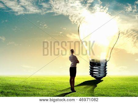 Imagen empresaria mirando la bombilla. Concepto de energía verde
