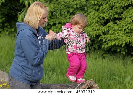 Baby walking on a tree trunk