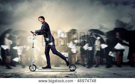 Image of young businessman in black suit riding scooter