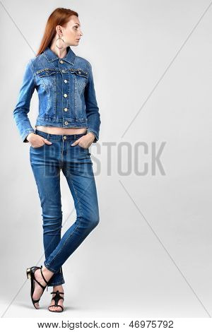 Beautiful woman in denim clothes on grey background. Space for text.