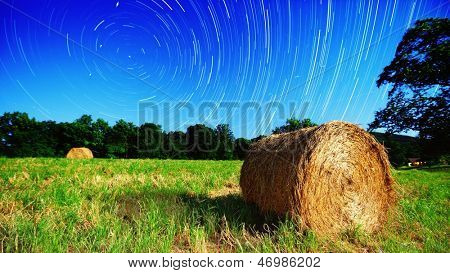 Moonlit hay bale under star trails on a farm in North Georgia, USA.