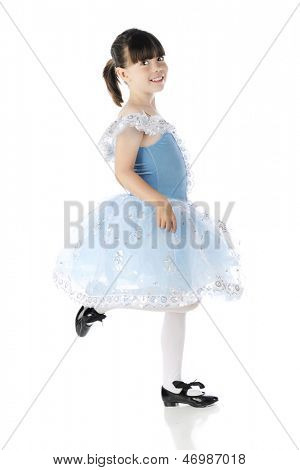 Full length image of a happy elementary girl tap dancing in a beautiful blue and silver dress. On a white background.