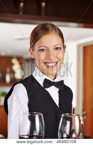 Happy waiter with two red wine glasses in hotel