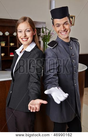 Smiling receptionist and happy bellboy in hotel offering a welcome