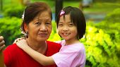 image of piety  - Grand daughter hugging Grandmother in the park - JPG