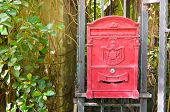picture of postbox  - Traditional old English red postbox hang on gate - JPG