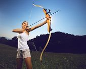stock photo of archer  - Attractive female archer bending a bow and aiming in the sky - JPG