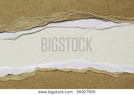 Hole ripped in brown paper on white background