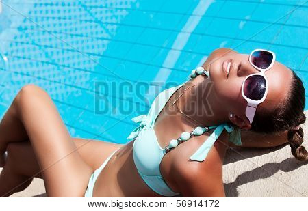 Beautiful Young Woman Relaxing Near The Swimming Pool