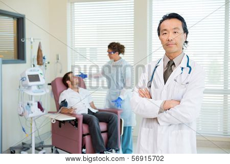 Portrait of male doctor with nurse and chemo patient in background.