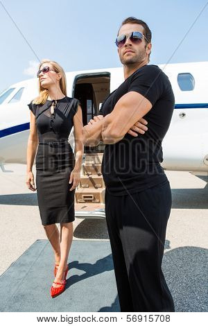 Elegant woman with bodyguard standing against private jet