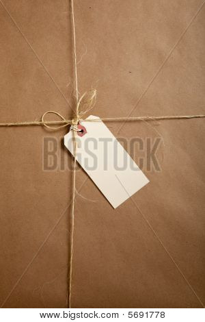 A Shipping Box Ties With String With A Blank Label