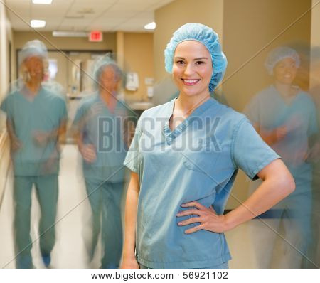 Portrait of happy young doctor with team walking in background at hospital corridor