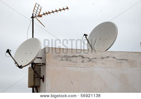 Antennas on a Roof over Cloudy Sky