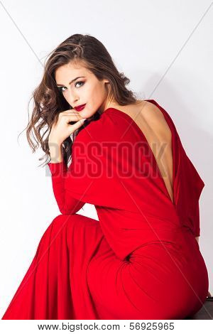 young elegant woman in red dress sit on chair studio shot