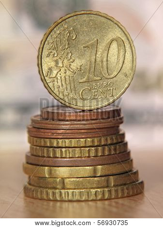Ten Euro Cent Coin Balancing On A Top Of Coins Stack.